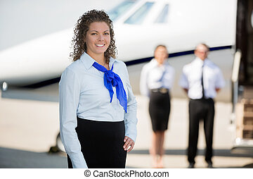 Portrait of confident airhostess smiling while pilot and colleague standing by private jet at airport terminal