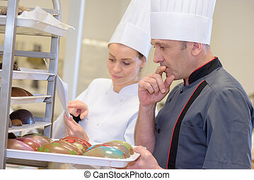 portrait of confident bakers packing pastries in bakery