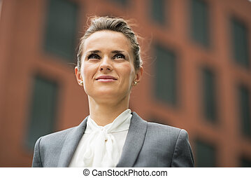 Portrait of confident business woman in front of office...