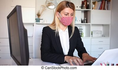 Portrait of confident businesswoman wearing cloth facial mask working on laptop in business office
