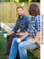 Portrait of confident carpenter holding disposable coffee cup while sitting with coworker on wooden frame