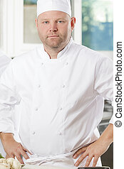 Portrait of confident chef in large kitchen