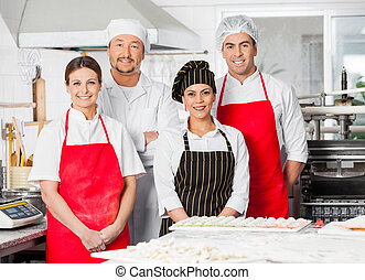 Portrait Of Confident Chef Team Standing In Kitchen