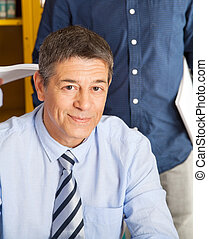 Portrait of confident college teacher smiling with student standing in background at library