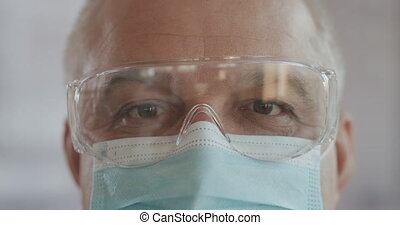 Portrait of confident doctor woman face, close-up. eyes with safety glasses and protective mask. Research Laboratory Officer. 2019 Novel Coronavirus (2019-nCoV), COVID-19, pandemic, isolation concept.