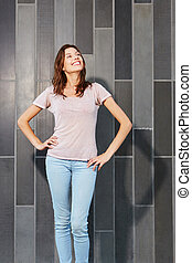 confident female fashion model standing against a wall and looking away