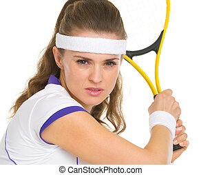 Portrait of confident female tennis player ready to hit ball