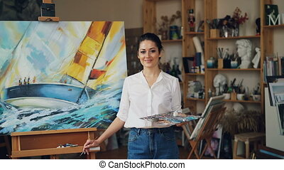Portrait of confident girl painter holding palette and...