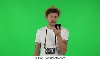 Portrait of confident guy is asking for information on the network via phone. Green screen