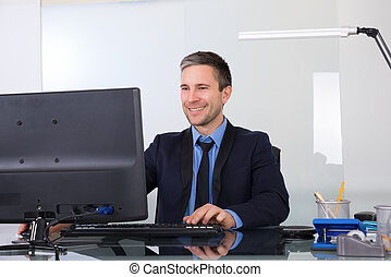 Happy Businessman Using Computer In His Office