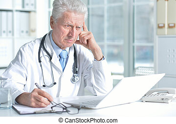 confident senior male doctor with stethoscope working in office