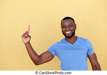 confident smiling man pointing finger up