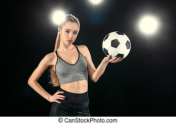 portrait of confident sporty holding soccer ball in hand on black