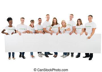 Portrait Of Confident Volunteers Holding Blank Billboard -...
