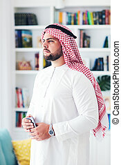 portrait of confident young adult arabic man at home