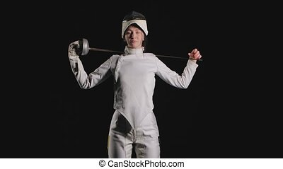 Portrait of confident young woman fencer. A sportswoman in a white suit with a sword in her hands looks straight and poses. Black background. Slow motion. Close up