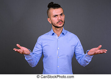 Portrait of confused bearded Turkish businessman shrugging shoulders