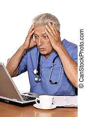 Portrait of confused doctor with a laptop on white background