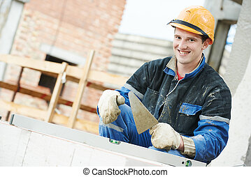Portrait of construction mason worker bricklayer installing brick with trowel putty knife outdoors
