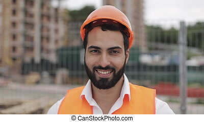 Portrait of construction worker in orange helmet smiling at the camera. The builder stands against the backdrop of a modern building. Slow motion.
