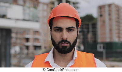 Portrait of construction worker on building site looking at the camera.