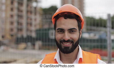 Portrait of construction worker on building site smiling at the camera.