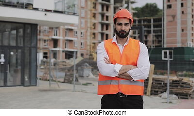 Portrait of construction worker on building site with crossed hands looking at the camera. Professions, construction, workers, architect concept.