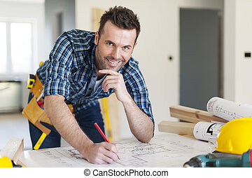 Portrait of construction worker with plans