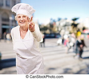 portrait of cook senior woman doing good gesture at crowded ...