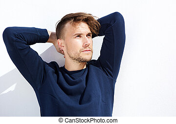 cool fashion guy looking away with hands behind head