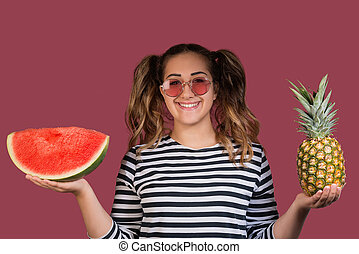 Portrait of cool girl in sunglasses holding the pineapple and slice of watermelon in her hands