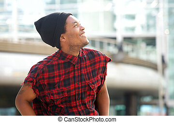 cool young african american man laughing outside in city