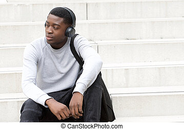 cool young african american man sitting on steps and listening to music with headphones