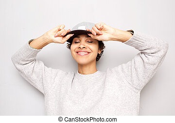 cool young african american woman smiling with cap against white background