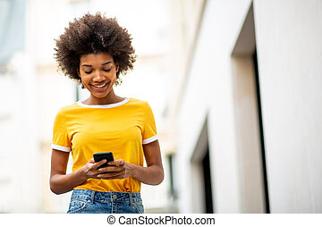 cool young african american woman walking with mobile phone