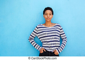 cool young african woman against blue background