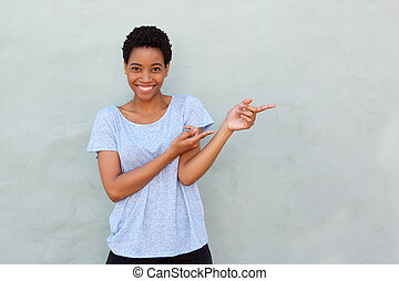 cool young black woman pointing fingers at copy space
