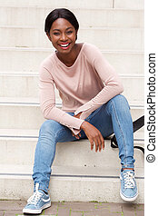cool young black woman sitting outside on steps