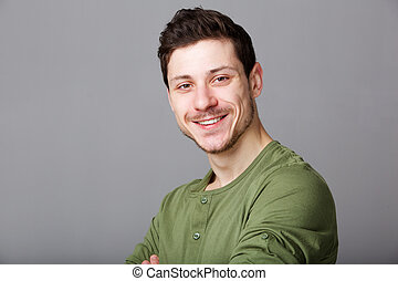 cool young man smiling against gray wall