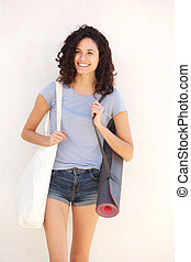 cool young woman smiling with bag and yoga mat against white background