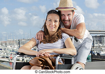 portrait of couple at a marina woman in wheelchair