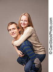 Portrait of couple, girl is on her boy's back