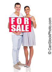couple holding a for sale sign