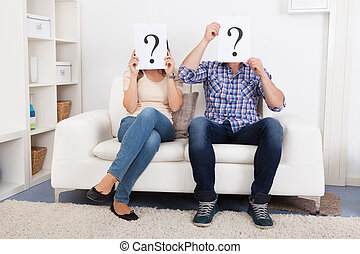 Couple Holding Question Mark Sign In Front Of Face -...