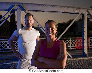 portrait of couple jogging across the bridge in the city