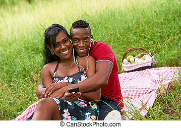 Portrait Of Couple Listening To Music On Mobile Phone