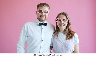 Portrait of couple man and woman in heart shape glasses ...