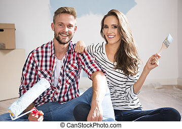 Portrait of couple painting their new apartment