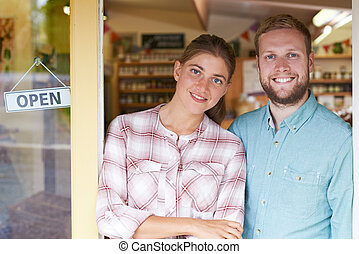 Portrait Of Couple Running Delicatessen Outside Store