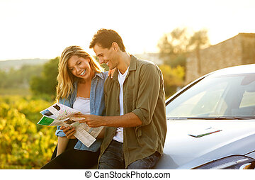couple sitting on car looking at map together